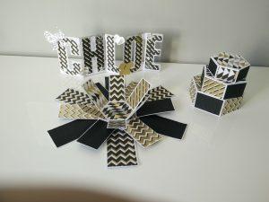 boîte à explosion ouverte et prénom chloé décorés . couleur or , noir et blanc