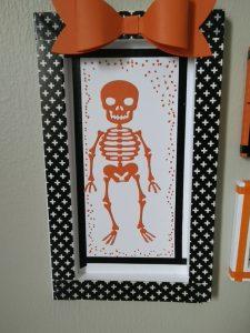 cadre blanc , masking tape noir, squelette orange , noeud papillon